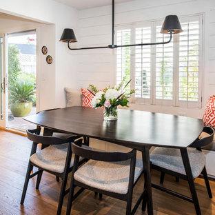 Foto di un angolo colazione minimal con pareti bianche, pavimento in legno massello medio e pareti in perlinato