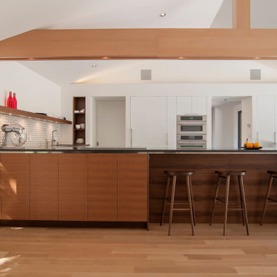 Inspiration for a large mid-century modern l-shaped marble floor, gray floor and vaulted ceiling kitchen remodel in Cleveland with a double-bowl sink, flat-panel cabinets, white cabinets, quartz countertops, yellow backsplash, ceramic backsplash, stainless steel appliances, a peninsula and gray countertops