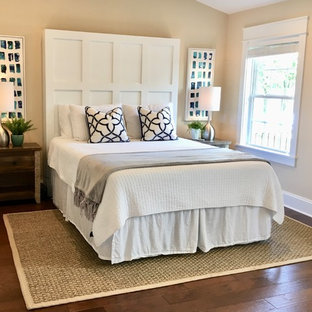 Photo of a mid-sized beach style master bedroom in Charlotte with yellow walls, medium hardwood floors and brown floor.