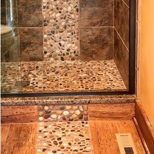 Foto di una stanza da bagno stile rurale di medie dimensioni con lavabo sottopiano, ante in legno bruno, top in granito, piastrelle marroni, piastrelle di ciottoli, pareti beige e pavimento in gres porcellanato