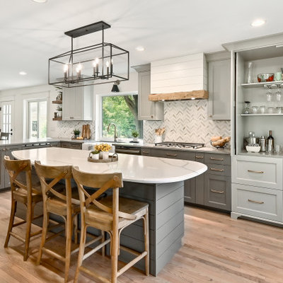 Example of a huge farmhouse l-shaped medium tone wood floor and brown floor eat-in kitchen design in Milwaukee with a farmhouse sink, shaker cabinets, gray cabinets, quartz countertops, white backsplash, marble backsplash, stainless steel appliances, an island and gray countertops