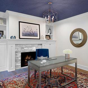 Inredning av ett klassiskt stort hemmabibliotek, med vita väggar, mellanmörkt trägolv, en standard öppen spis, ett fristående skrivbord och brunt golv