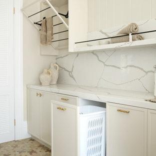 Rustik inredning av en stor vita vitt tvättstuga, med beige skåp, marmorbänkskiva, vitt stänkskydd, stänkskydd i marmor, beige väggar, klinkergolv i keramik, en tvättmaskin och torktumlare bredvid varandra och flerfärgat golv