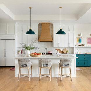 ミネアポリスの広いビーチスタイルのおしゃれなキッチン (アンダーカウンターシンク、フラットパネル扉のキャビネット、白いキャビネット、クオーツストーンカウンター、白いキッチンパネル、セラミックタイルのキッチンパネル、パネルと同色の調理設備、淡色無垢フローリング、茶色い床、白いキッチンカウンター、格子天井) の写真