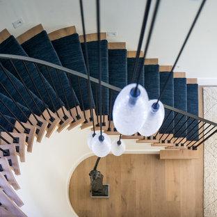 Ejemplo de escalera curva, mediterránea, grande, con escalones enmoquetados, contrahuellas enmoquetadas y barandilla de metal