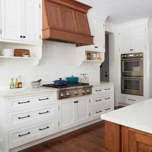 シカゴの広いカントリー風おしゃれなキッチン (エプロンフロントシンク、落し込みパネル扉のキャビネット、白いキャビネット、クオーツストーンカウンター、白いキッチンパネル、塗装板のキッチンパネル、シルバーの調理設備、無垢フローリング、茶色い床、白いキッチンカウンター) の写真