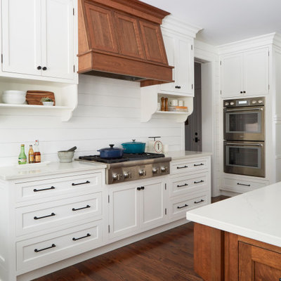 Large cottage u-shaped medium tone wood floor and brown floor open concept kitchen photo in Chicago with a farmhouse sink, recessed-panel cabinets, white cabinets, quartz countertops, white backsplash, shiplap backsplash, stainless steel appliances, an island and white countertops