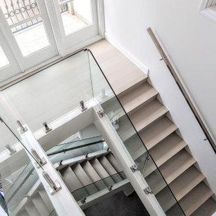 Immagine di una grande scala minimalista con pedata in legno, alzata in vetro e parapetto in metallo