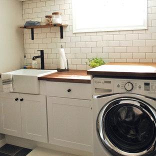 Ispirazione per una sala lavanderia chic di medie dimensioni con lavello stile country, ante in stile shaker, ante bianche, top in legno, pareti grigie, pavimento con piastrelle in ceramica, lavatrice e asciugatrice affiancate e pavimento grigio