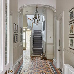 Пример оригинального дизайна: большой коридор с бежевыми стенами, полом из терракотовой плитки, разноцветным полом, потолком с обоями, обоями на стенах и правильным освещением