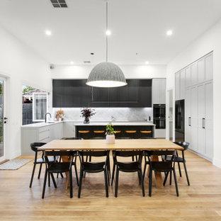 Exempel på ett stort modernt grå grått kök, med en dubbel diskho, skåp i shakerstil, marmorbänkskiva, grått stänkskydd, stänkskydd i marmor, svarta vitvaror, ljust trägolv och en köksö