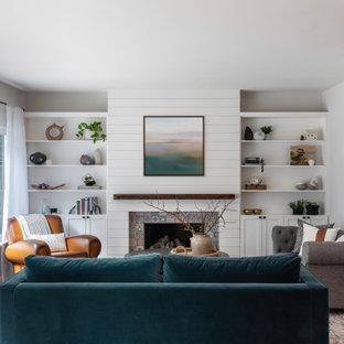 Mittelgroßes, Repräsentatives, Fernseherloses, Offenes Landhausstil Wohnzimmer mit grauer Wandfarbe, dunklem Holzboden, Kamin, Kaminumrandung aus Holzdielen, braunem Boden und Holzdielenwänden in San Francisco