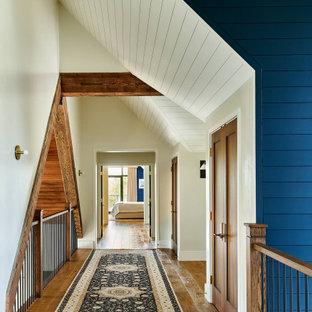 デンバーの広いカントリー風おしゃれな廊下 (マルチカラーの壁、無垢フローリング、茶色い床、塗装板張りの天井、塗装板張りの壁) の写真