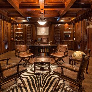 ヒューストンの巨大なラスティックスタイルのおしゃれな書斎 (茶色い壁、無垢フローリング、標準型暖炉、自立型机、漆喰の暖炉まわり) の写真