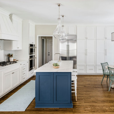 Mid-sized transitional l-shaped medium tone wood floor and brown floor eat-in kitchen photo in Charlotte with a farmhouse sink, shaker cabinets, white cabinets, quartz countertops, gray backsplash, porcelain backsplash, stainless steel appliances, an island and white countertops