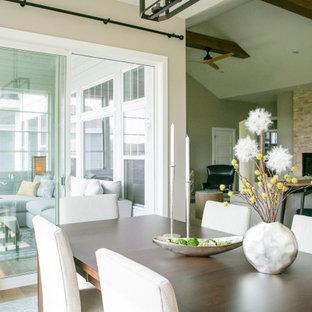 Пример оригинального дизайна: большая гостиная-столовая в современном стиле с паркетным полом среднего тона, двусторонним камином, фасадом камина из каменной кладки и балками на потолке