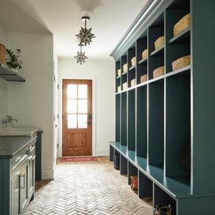 Ejemplo de vestíbulo posterior de estilo de casa de campo, grande, con paredes blancas, suelo de ladrillo, puerta simple, puerta de madera en tonos medios y suelo rojo
