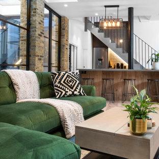 Exemple d'un sous-sol industriel semi-enterré et de taille moyenne avec un bar de salon, un mur blanc, un sol en bois peint, un sol beige, un plafond voûté et un mur en parement de brique.