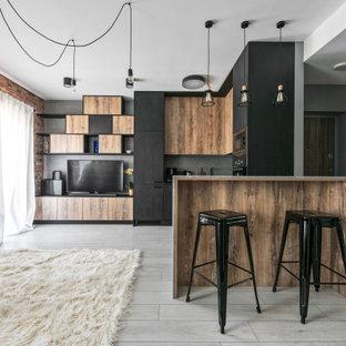 Свежая идея для дизайна: большая угловая кухня в современном стиле с плоскими фасадами, фасадами цвета дерева среднего тона, серым фартуком, техникой под мебельный фасад, полуостровом, серым полом и черной столешницей - отличное фото интерьера