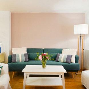 Ispirazione per un piccolo soggiorno design aperto con pareti rosa, pavimento in legno massello medio e pavimento marrone