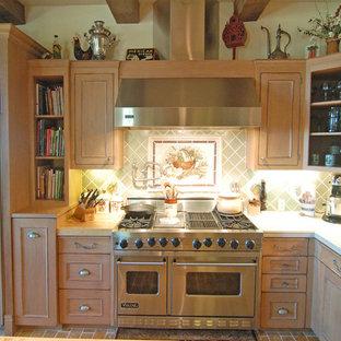 サンルイスオビスポの大きい地中海スタイルのおしゃれなキッチン (ドロップインシンク、インセット扉のキャビネット、中間色木目調キャビネット、タイルカウンター、緑のキッチンパネル、セラミックタイルのキッチンパネル、シルバーの調理設備の、レンガの床) の写真