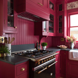 Design ideas for a small traditional l-shaped separate kitchen in Seattle with a farmhouse sink, shaker cabinets, pink cabinets, granite benchtops, pink splashback, timber splashback, panelled appliances, light hardwood floors, no island, brown floor and black benchtop.
