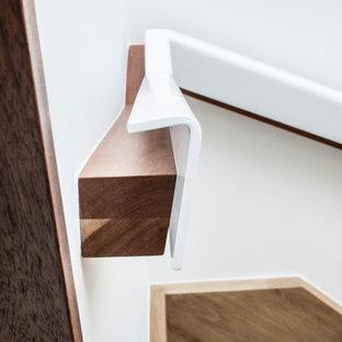 Foto di una piccola scala sospesa design con pedata in legno e parapetto in materiali misti