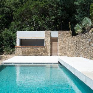Ejemplo de piscina alargada, mediterránea, grande, rectangular, en patio delantero, con losas de hormigón