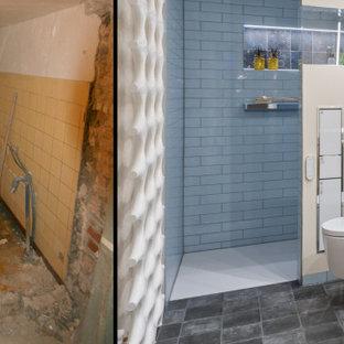 Modelo de cuarto de baño con ducha, contemporáneo, de tamaño medio, con armarios con paneles lisos, puertas de armario de madera clara, ducha a ras de suelo, sanitario de pared, baldosas y/o azulejos marrones, baldosas y/o azulejos de cerámica, paredes beige, lavabo sobreencimera, encimera de piedra caliza, ducha abierta y encimeras negras