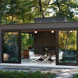 Foto di un piccolo patio o portico minimalista dietro casa con lastre di cemento e un tetto a sbalzo