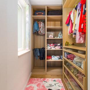 Kleiner Moderner Begehbarer Kleiderschrank mit flächenbündigen Schrankfronten, hellbraunen Holzschränken und Teppichboden in Sonstige