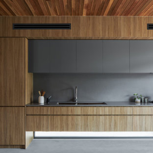 Inspiration for a modern galley kitchen in Brisbane with an undermount sink, flat-panel cabinets, light wood cabinets, grey splashback, panelled appliances, with island, grey floor, grey benchtop and wood.
