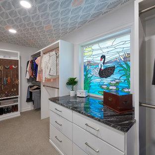 Ispirazione per uno spazio per vestirsi unisex minimalista di medie dimensioni con ante lisce, ante bianche, pavimento beige e soffitto in carta da parati