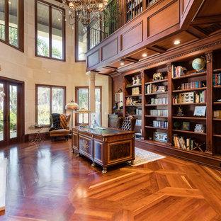 Esempio di un ampio studio mediterraneo con libreria, pareti beige, pavimento in legno massello medio, camino classico, cornice del camino in pietra, scrivania autoportante e pavimento marrone