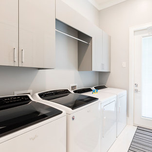 This is an example of a large modern single-wall separated utility room in Orlando with flat-panel cabinets, grey cabinets, grey walls, porcelain flooring, a side by side washer and dryer and white floors.