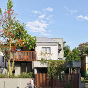 Inspiration for a contemporary two-storey stucco beige house exterior in Brisbane with a metal roof, a grey roof and board and batten siding.