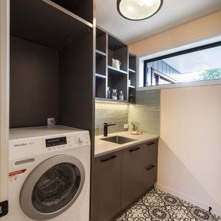 Modern inredning av en beige beige tvättstuga enbart för tvätt, med en enkel diskho, släta luckor, bruna skåp, laminatbänkskiva, grönt stänkskydd, stänkskydd i keramik, klinkergolv i keramik och en tvättpelare