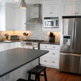 Inredning av ett klassiskt mellanstort kök, med en rustik diskho, skåp i shakerstil, vita skåp, bänkskiva i koppar, grått stänkskydd, stänkskydd i tunnelbanekakel, rostfria vitvaror, mellanmörkt trägolv, en köksö och svart golv