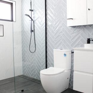 Diseño de cuarto de baño con ducha, único y flotante, moderno, de tamaño medio, con armarios con paneles lisos, puertas de armario blancas, ducha abierta, sanitario de una pieza, paredes azules, suelo de baldosas de porcelana, lavabo sobreencimera, encimera de cobre, suelo negro, ducha abierta y encimeras blancas