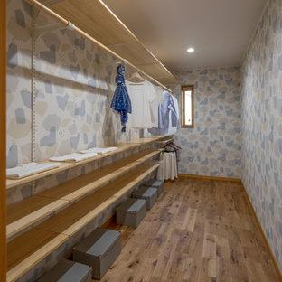 Ispirazione per una cabina armadio per donna scandinava di medie dimensioni con pavimento in legno massello medio, soffitto in carta da parati e pavimento marrone