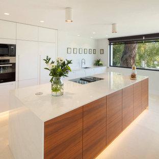 Modelo de cocina lineal, contemporánea, grande, abierta, con fregadero encastrado, armarios con paneles lisos, puertas de armario de madera clara, electrodomésticos negros, suelo de mármol, una isla y suelo beige