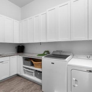 Esempio di una grande sala lavanderia moderna con lavello da incasso, ante in stile shaker, ante bianche, top in granito, pareti bianche, pavimento in vinile, lavatrice e asciugatrice affiancate, pavimento grigio e top blu