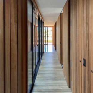 Cette photo montre un couloir tendance de taille moyenne avec un mur marron, un sol en bois clair, un sol marron, un plafond en lambris de bois et boiseries.
