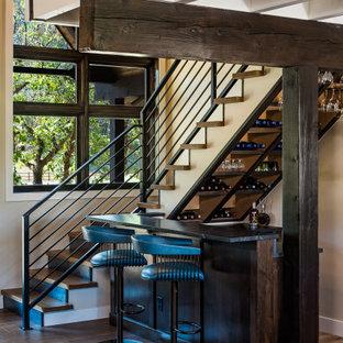 Idee per un piccolo bancone bar stile rurale con ante in stile shaker, ante in legno bruno, top in granito, paraspruzzi nero, paraspruzzi in granito, pavimento in legno massello medio, pavimento marrone e top nero