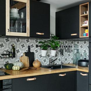 Источник вдохновения для домашнего уюта: угловая кухня среднего размера в стиле лофт с обеденным столом, врезной раковиной, плоскими фасадами, черными фасадами, деревянной столешницей, разноцветным фартуком, фартуком из керамической плитки, черной техникой, полом из керамической плитки, синим полом и коричневой столешницей без острова