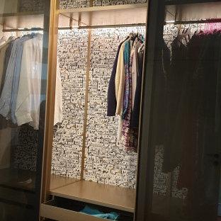 Cette photo montre un dressing room moderne de taille moyenne et neutre avec un placard à porte vitrée, des portes de placard marrons, un sol en brique et un sol marron.