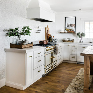 Photo of a mid-sized country u-shaped kitchen in Other with a farmhouse sink, shaker cabinets, white cabinets, concrete benchtops, white splashback, marble splashback, white appliances, laminate floors, with island and white benchtop.