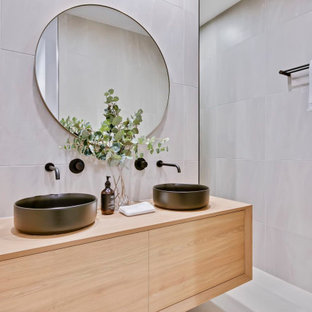 Contemporary bathroom in Sunshine Coast with flat-panel cabinets, light wood cabinets, gray tile, grey walls, a vessel sink, wood benchtops, white floor, a double vanity and a floating vanity.