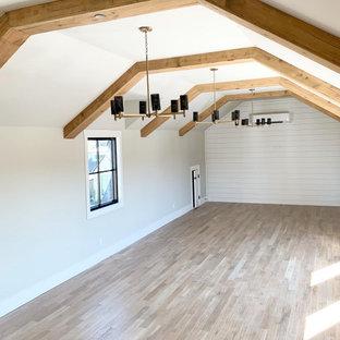 Großer Landhaus Yogaraum mit weißer Wandfarbe, hellem Holzboden, braunem Boden und freigelegten Dachbalken in Dallas
