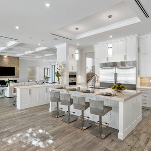 Photo of a large transitional l-shaped open plan kitchen in Miami with a farmhouse sink, beaded inset cabinets, white cabinets, quartzite benchtops, beige splashback, granite splashback, stainless steel appliances, light hardwood floors, multiple islands, beige floor, white benchtop and coffered.